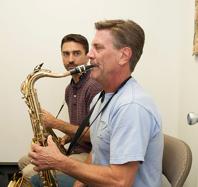 Adult taking private music lesson on saxophone.