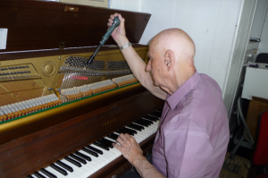 Piano technician tuning a piano
